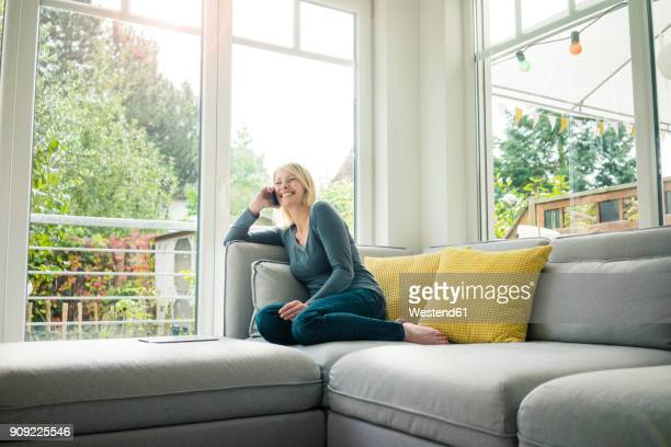 Happy woman on the phone on couch