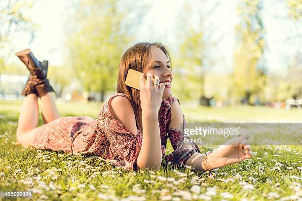 Happy woman on the phone relaxing in grass during springtime.
