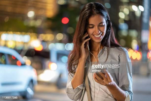 gelukkige vrouw op straat bij nacht die op haar mobiele telefoon met oortelefoons spreekt - voip stockfoto's en -beelden