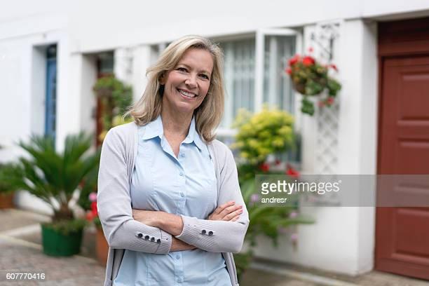 Femme heureuse en dehors de sa maison