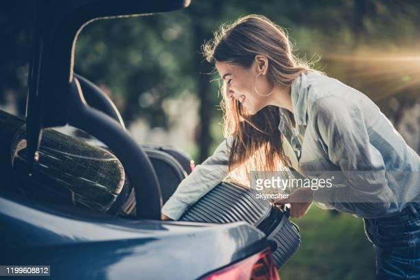 happy woman packing her suitcase into the car trunk. - só adultos imagens e fotografias de stock