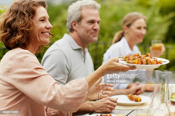 Happy woman passing dish at outdoor lunch table
