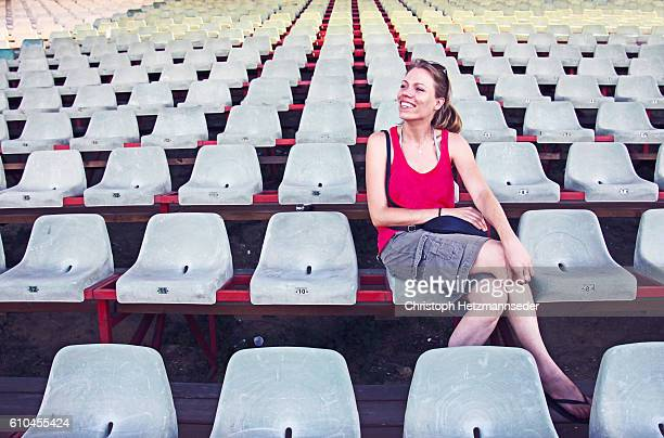 happy woman - empty bleachers stockfoto's en -beelden