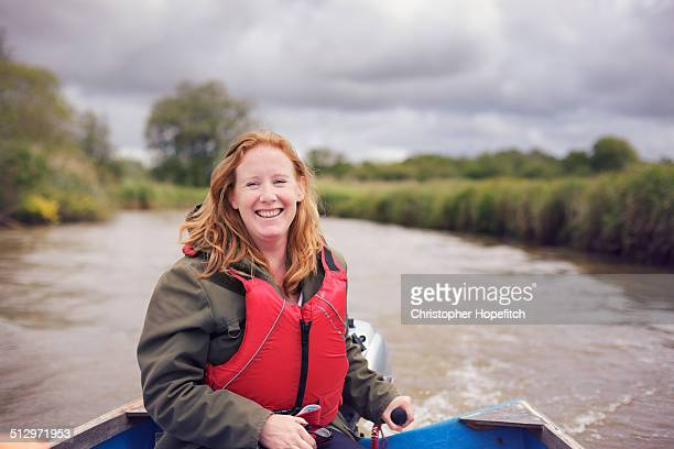 Happy woman piloting small boat