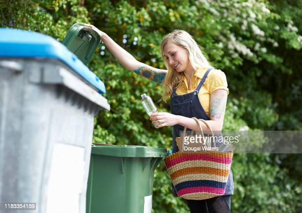 happy woman placing plastic bottle into recycling bin. - rubbish bin stock pictures, royalty-free photos & images