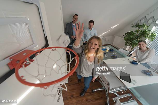 Happy woman playing basketball in conference room