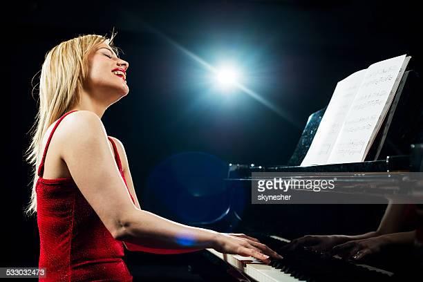 Feliz mulher a tocar piano.