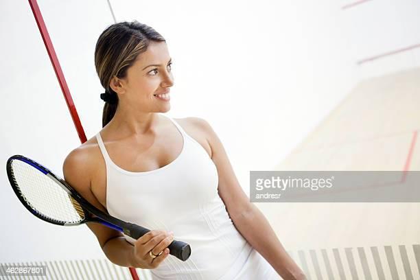 Happy woman playing squash