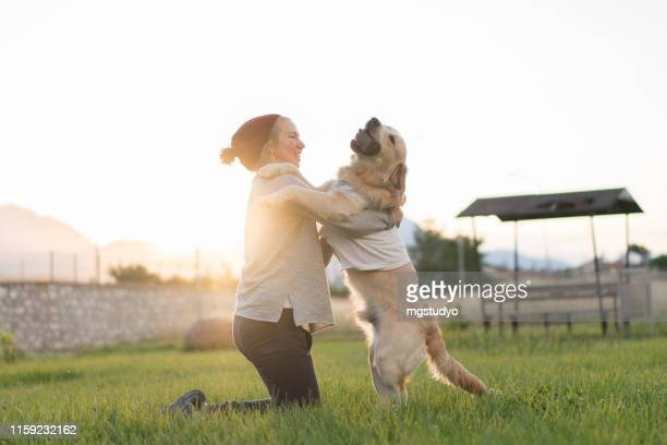 happy woman plays with her adorable dog in park - off leash dog park stock pictures, royalty-free photos & images