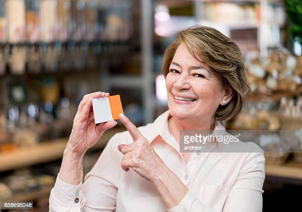 Happy woman pointing at a business card