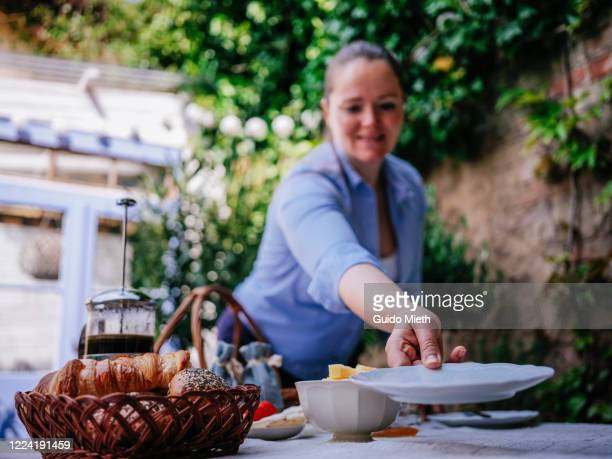 happy woman prepare breakfast in garden house. - guido mieth stock pictures, royalty-free photos & images