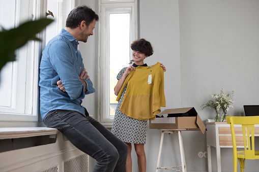 Happy woman presenting her new pullover at home - gettyimageskorea