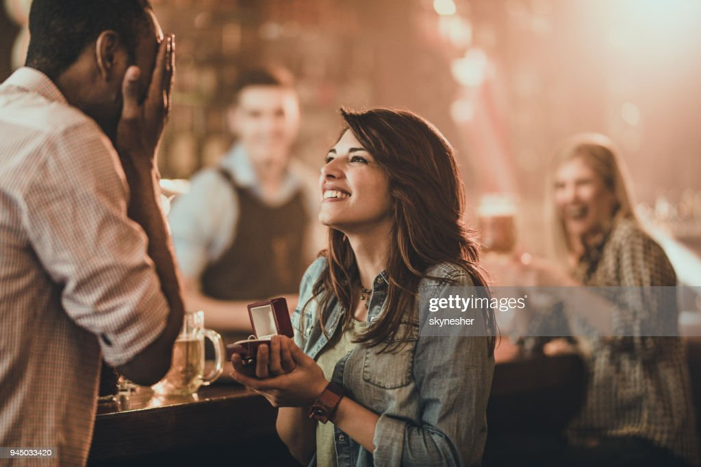 Happy woman proposing to her boyfriend in a bar. : Stock Photo