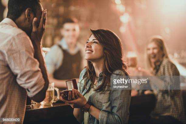 happy woman proposing to her boyfriend in a bar. - fidanzato foto e immagini stock