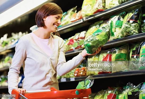 Happy woman purchasing a packet of vegetables