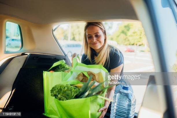 happy woman putting in the trunk bags with groceries after shopping - boot stock pictures, royalty-free photos & images