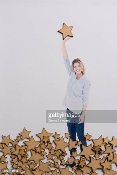 Happy woman reach up to touch a star