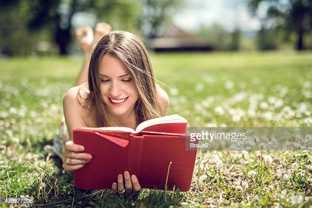 Mujer feliz leyendo un libro durante la primavera en la naturaleza.