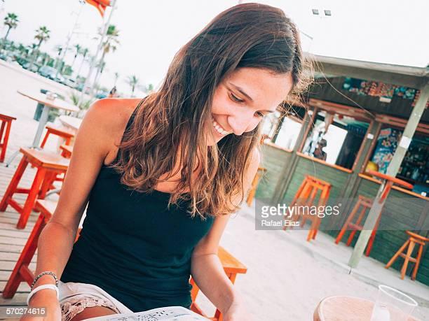Happy woman reading magazine at the beach bar