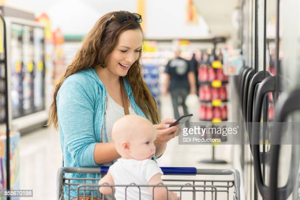 Happy woman reads shopping list on smart phone