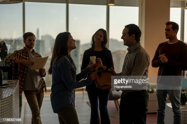 happy woman receiving a gift from her office friends for her birthday - hispanolistic stock photos and pictures