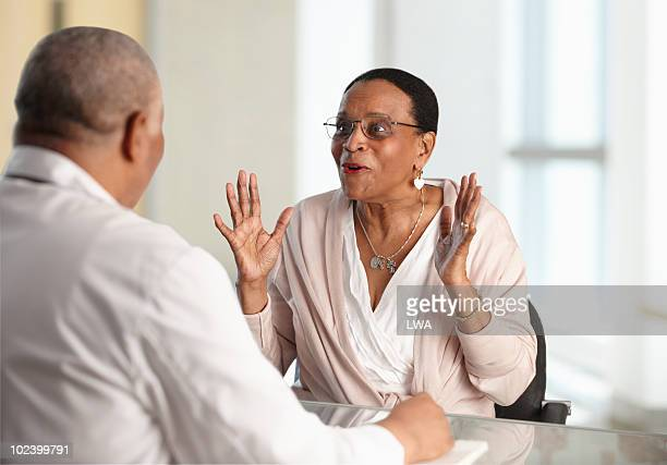 Happy Woman Receiving Good News From Doctor