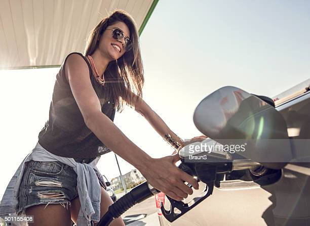 Happy woman refueling the gas tank at fuel pump.