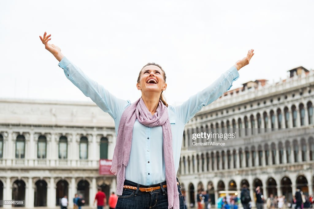 Happy woman rejoicing on piazza san marco in venice, italy : Stock Photo