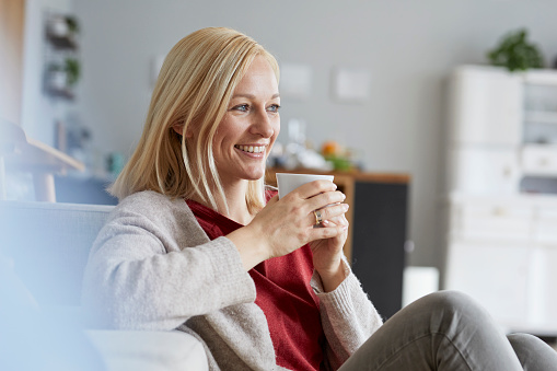 Happy woman relaxing at home, drinking coffee - gettyimageskorea