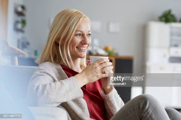 Happy woman relaxing at home, drinking coffee