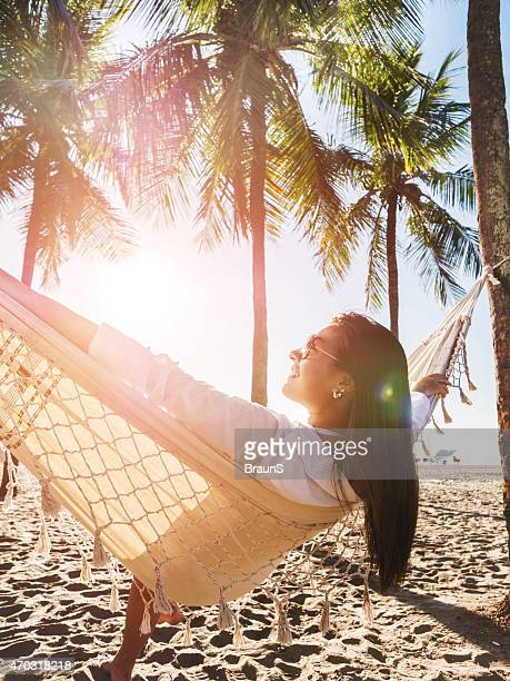 Happy woman relaxing in hammock at the beach.