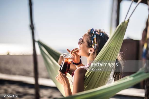 femme heureuse se détendre dans le hamac sur la plage et profiter dans sa boisson d'été. - hamac photos et images de collection