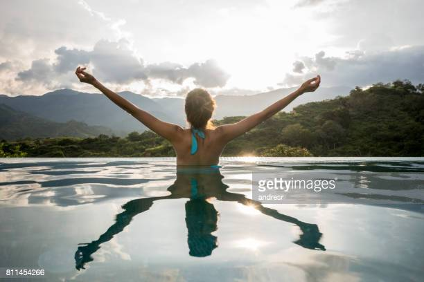 happy woman relaxing in the pool with arms up - south america stock pictures, royalty-free photos & images