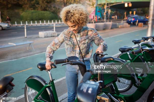 happy woman renting bicycle on city street - borrowing stock pictures, royalty-free photos & images