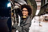 Happy woman repairing aircraft