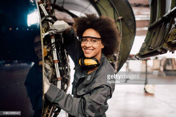happy woman repairing aircraft - aircraft stock photos and pictures
