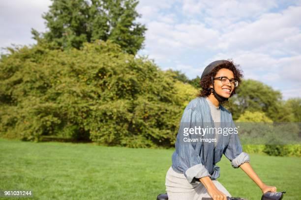 happy woman riding bicycle in park - human powered vehicle fotografías e imágenes de stock