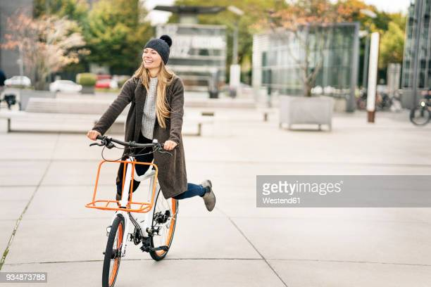 happy woman riding bicycle in the city - fahrrad stock-fotos und bilder