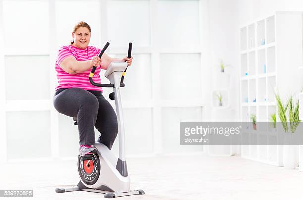 Happy woman riding exercise bike and looking at the camera.