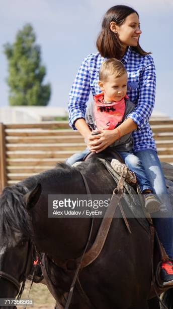 Happy Woman Riding Horse With Boy At Ranch On Sunny Day