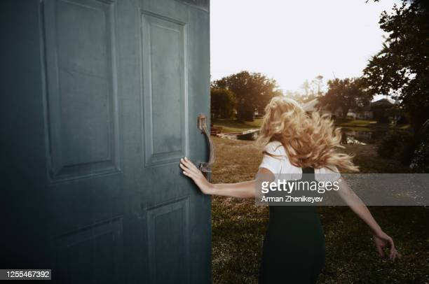 happy woman running next to the open door. nicely fits for book cover - runaway stock pictures, royalty-free photos & images