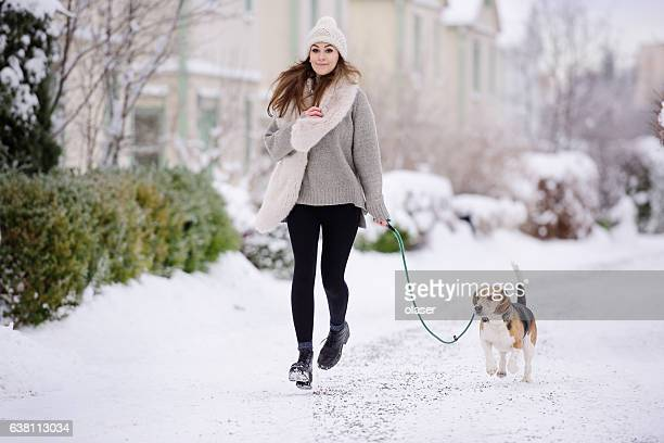 Happy woman running with beagle dog on winter street