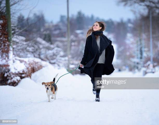 Gelukkige vrouw waarop winter straat met beagle hond