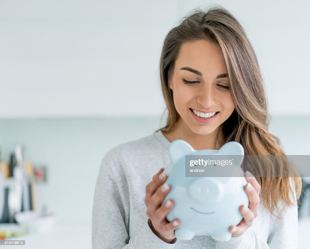 Happy woman saving money in a piggybank : Foto de stock