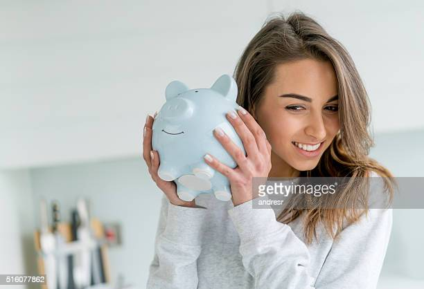 happy woman saving money in a piggybank - ersparnisse stock-fotos und bilder