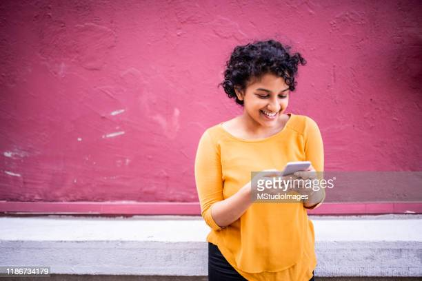 happy woman sending a text to her friend - building feature stock pictures, royalty-free photos & images