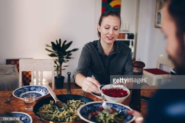 happy woman serving cherry tomatoes to man in plate at home - vegetarisch gerecht stockfoto's en -beelden