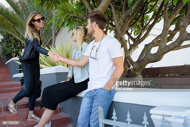 happy woman shaking hands with friends on stairs - boyfriend stock pictures, royalty-free photos & images