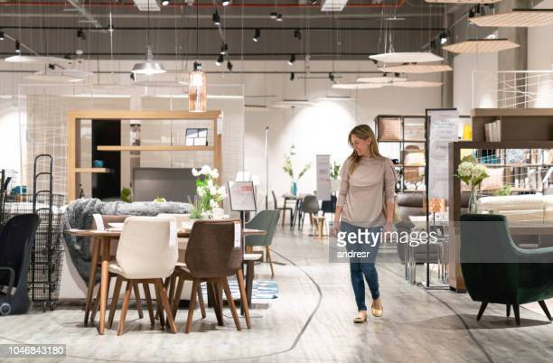 happy woman shopping at a furniture store - showroom stock pictures, royalty-free photos & images