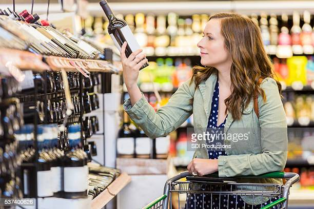 Happy woman shopping for red wine